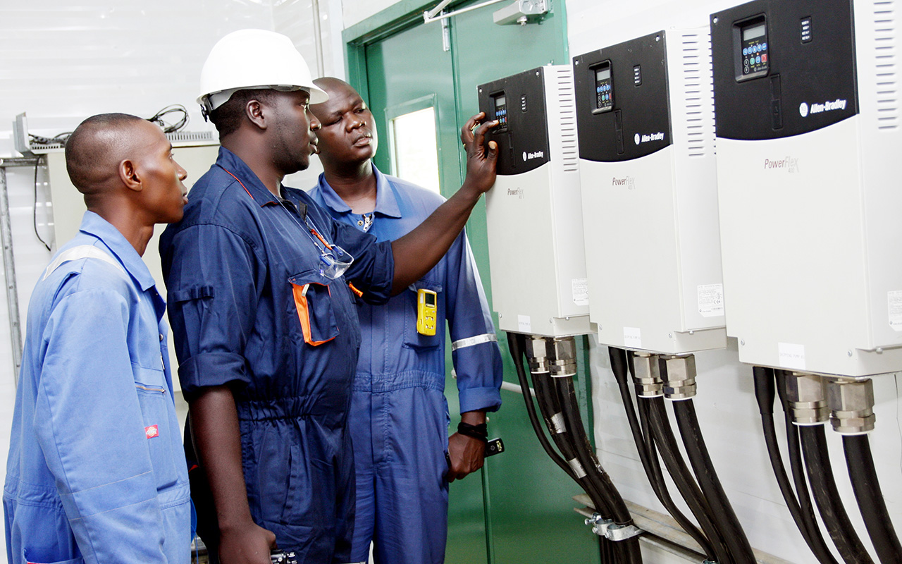 A group of petrochemical technicians looking at a control panel